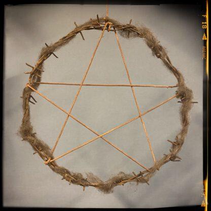 Pentagrammi piikkilankakehällä